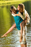Girl piggyback riding his boyfriend in water Stock Photo