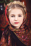 Girl with a pigtail in colored headscarf. Portrait of a girl with a pigtail around her head in a multicolored headscarf. Closeup. Studio photography in rustic Stock Photos