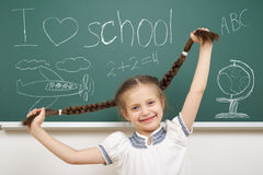 Girl with pigtail drawing on school board Royalty Free Stock Photos
