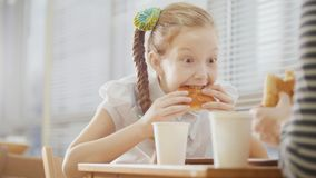 Girl with pigtail is eating sweets in the cafe. Close up Stock Photo
