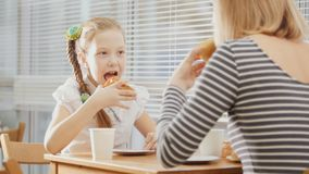 Girl with pigtail is eating sweets in the cafe. Close up Royalty Free Stock Photography