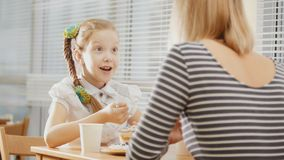 Girl with pigtail with her mum in the cafe - teen feels surprised. Close up Stock Images