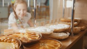 Girl with a pigtail looks at the pies in the window choosing, de-focused. Girl with a pigtail looks at the pies in the window choosing, the girl on the other Royalty Free Stock Photo