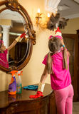 Girl with pigtails cleaning lamp with feather brush Stock Photography