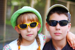 The girl with pigtails embraces brother. Both have sunglasses royalty free stock images