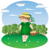 A girl with pigtails in a green dress and a hat with a basket in a clearing dotted with flowers, behind a forest and sky. With clouds Royalty Free Stock Image