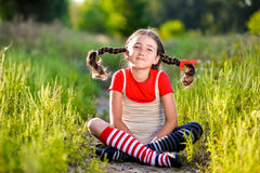 Girl with pigtails imagines the summer on the nature stock images