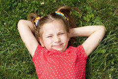 Girl with pigtails lying on grass Royalty Free Stock Photo