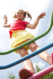 Girl with pigtails plays on the playground Stock Photo