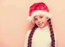 Girl with pigtails in Santa Claus hat Royalty Free Stock Image