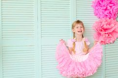 Girl with pigtails, wearing a skirt tutu. Beautiful girl with pigtails, wearing a skirt tutu, against a light green wall stock photos