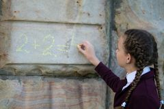 Girl with pigtails, wrote a mathematical example on a stone wall. schoolgirl royalty free stock image