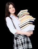 Girl with a pile of books in hands on black Royalty Free Stock Photos