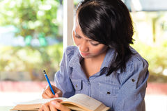 Girl with pile of books learning Stock Image
