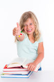 Girl with a pile of books and thumb up Stock Image
