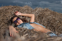 Girl on the pile of hay Royalty Free Stock Image