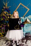 Smiling girl with a pillow against the Christmas tree background stock image