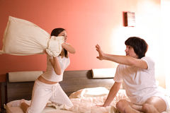 Girl with pillow and boy Royalty Free Stock Photos