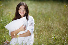 The girl with a pillow on the fresh spring grass. Stock Images