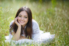 The girl with a pillow on the fresh spring grass. Stock Photography
