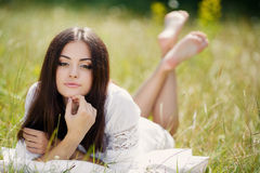 The girl with a pillow on the fresh spring grass. Royalty Free Stock Photos
