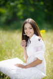 The girl with a pillow on the fresh spring grass. Royalty Free Stock Photography