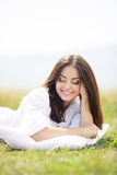 The girl with a pillow on the fresh spring grass. Royalty Free Stock Image