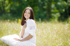 The girl with a pillow on the fresh spring grass. Stock Photos