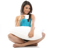 Girl with pillow having cup of coffee Royalty Free Stock Photos