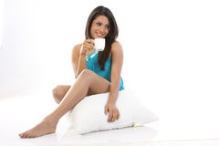 Girl with pillow having cup of coffee Stock Image