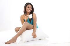 Girl with pillow having cup of coffee Stock Images