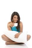 Girl with pillow holding coffee cup Stock Image