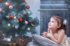 Girl on pillow looks thoughtfully out window at background of Christmas tree Royalty Free Stock Image