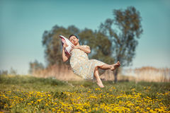 Girl with pillow soars. Girl lying on a cushion hovers over the field in weightlessness Royalty Free Stock Photo
