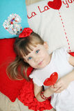 Girl on the pillows holding a lollipop Stock Image