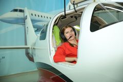 Girl pilot in headphones in a sports plane at the airport is a lifestyle stock photos