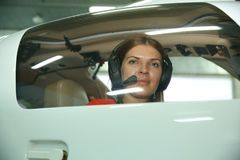 Girl pilot looks out the sports airplane window stock image