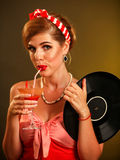 Girl pin-up style keeps vinyl record drink martini cocktail . Royalty Free Stock Photo