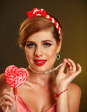 Girl in pin-up style lick striped lollipops. Stock Photo