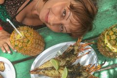 Girl with pina colada pineapple and table with lobster. The concept of travel stock photography
