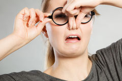 Girl pinches her nose because of stench stink. Royalty Free Stock Image