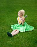 Girl with pineapple. Funny girl wearing green yellow dress holding pineapple stock photo