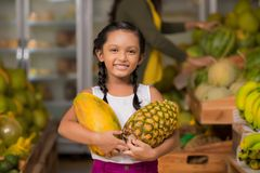Girl with pineapple and melon. Portrait of happy Indian girl with pineapple and melon in her hands Royalty Free Stock Photography