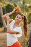 Girl with pineapple near the tree Stock Photos