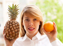 Girl with pineapple and orange Stock Images
