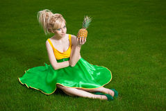 Girl with pineapple sitting on lawn. Funny girl wearing green yellow dress holding pineapple stock image