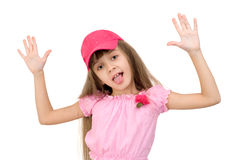 The girl in pink. The girl in a pink suit and a red cap has arranged hands and shows tongue Royalty Free Stock Photography