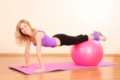 Girl with pink ball exercising. Young beautiful fitness girl with pink ball exercising in the gym stock image