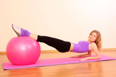 Girl with pink ball exercising. Young beautiful fitness girl with pink ball exercising stock photography