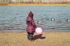 Girl with a pink baloon on riverbank. Little girl with a pink balloon standing on a riverbank in spring time Royalty Free Stock Photography